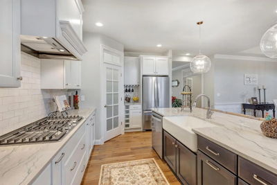 white kitchen with backsplash and pantry