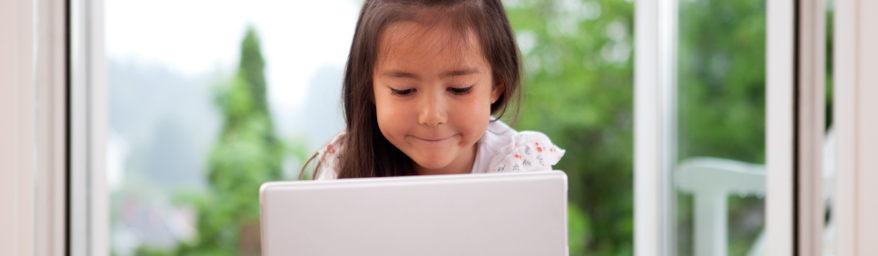 Young girl smiles at laptop.