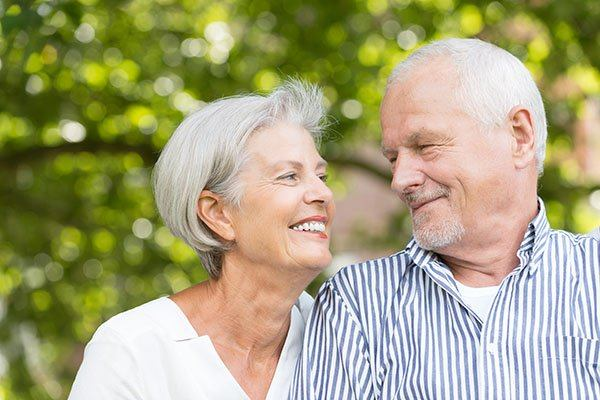 elderly couple looking at each other and smiling