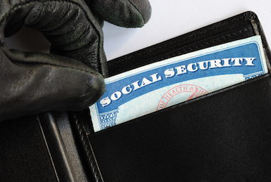 Image of gloved hand pulling a social security card out of a wallet