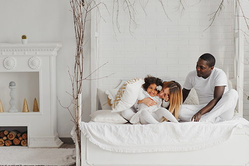 happy-interracial-couple-with-their-little-daughter-at-home-bedroom