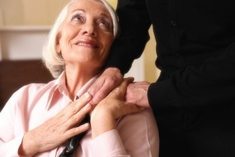 elderly woman with someone's hand on her shoulder