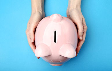 Female hands holding pink piggy bank on blue background