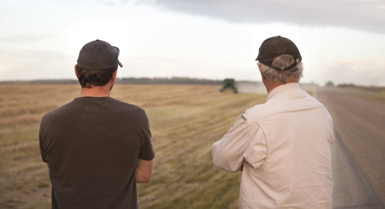 two farmers watching harvester