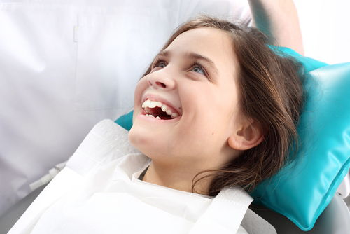 Little girl smiling in chair at dentist