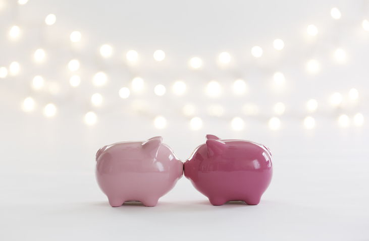 Two pink piggy banks sharing a kiss under string lights