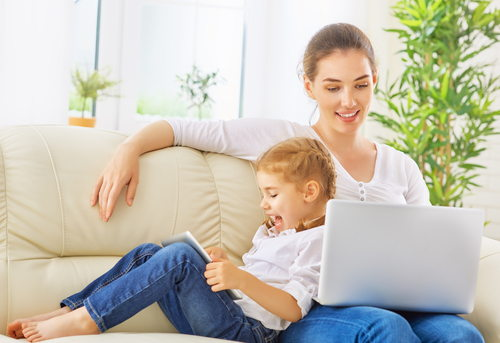 Mother on a laptop with daughter next to her