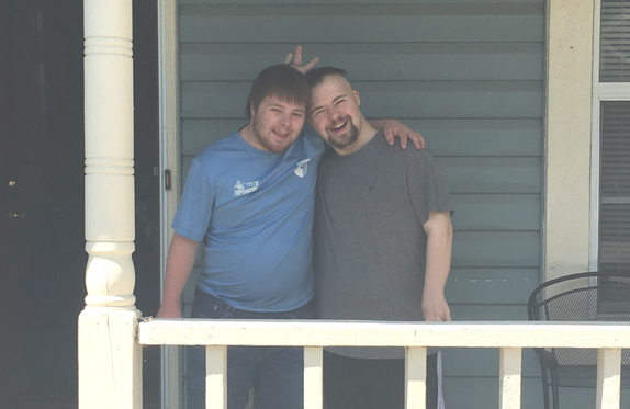 two young men standing on a porch