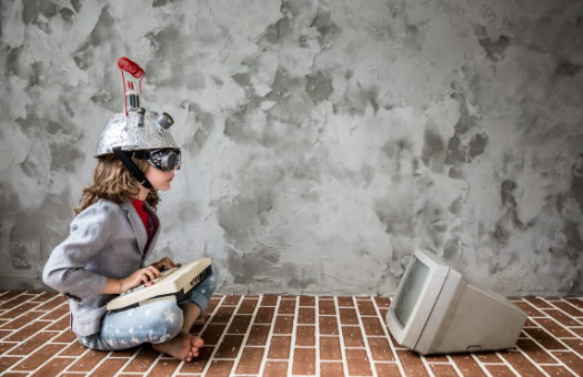 tween girl sitting on a brick floor with a colander covered in foil and an antenna wearing goggles, her legs are crossed and there is an 80's style monitor in front of her with a keyboard in her lap