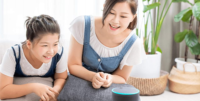 Women and daughter speaking to smart speaker