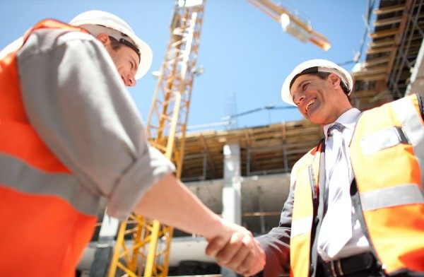 Image of two men shaking hands on a construction site