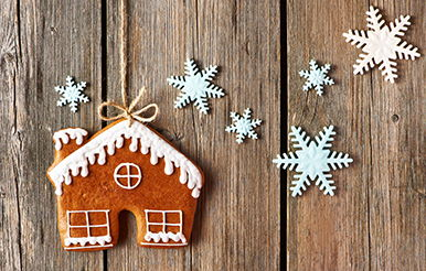 Gingerbread house on string with snowflakes against a wooden background