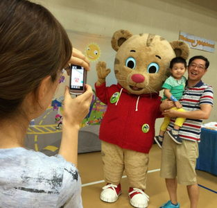 Family poses with Daniel Tiger at 2016 Be My Neighbor Day