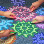 Child hands drawing gears with sidewalk chalk