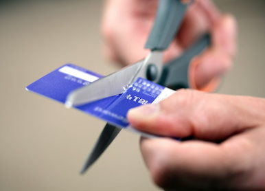 Image of person cutting up credit card