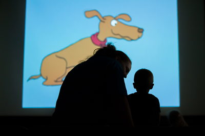 Parent and child watching a cartoon during a library program