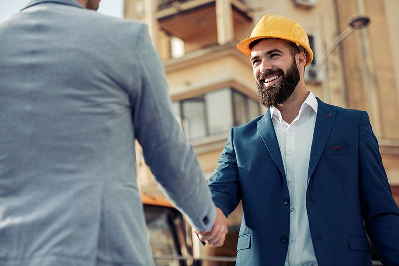 men in hard hats shaking hands