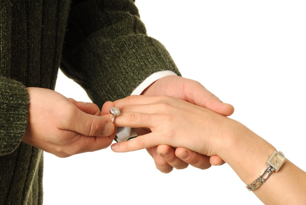 man putting ring on woman finger