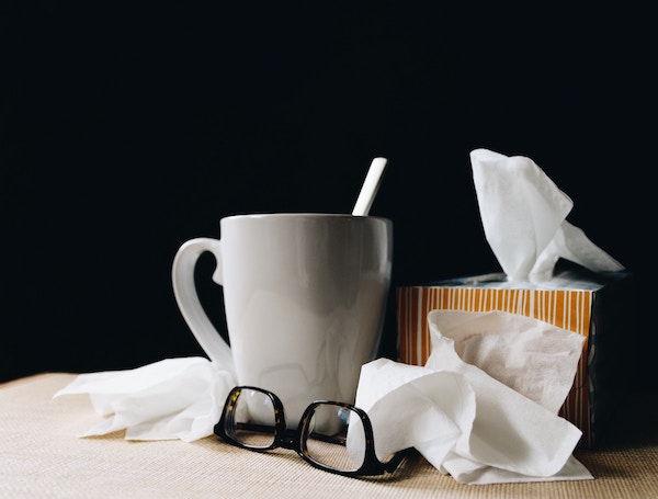 tissues, cup of tea, eyeglasses