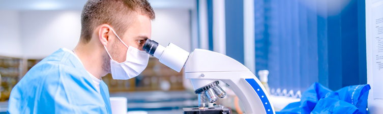 Male medical professional looking into a microscope