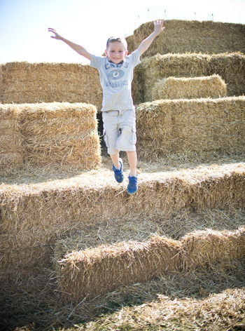child jumping off a hay bale