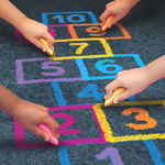 Children hands writing numbers with sidewalk chalk