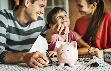 Mom, dad, and young son place coins into piggy bank.
