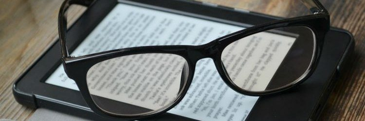 Black glasses resting on top of a Kindle
