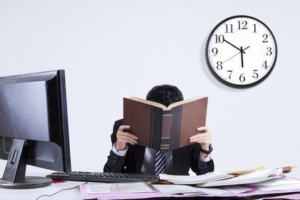 man with face stuck in book at office with clock in background