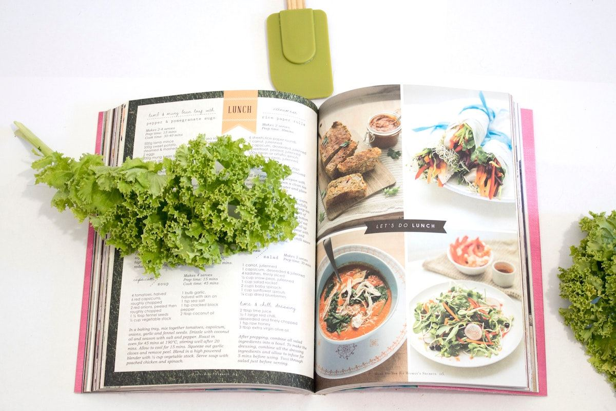 Overhead shot of a colorful recipe book with a piece of kale laying overtop.