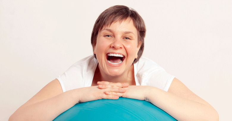 Woman smiling using exercise ball