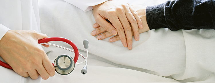 Close up of two individuals holding hands with stethoscope