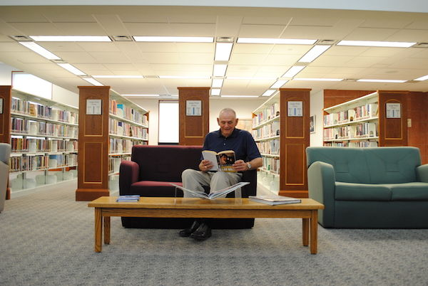 Man reading a book at the library