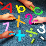 Children hands writing letters and numbers with sidewalk chalk