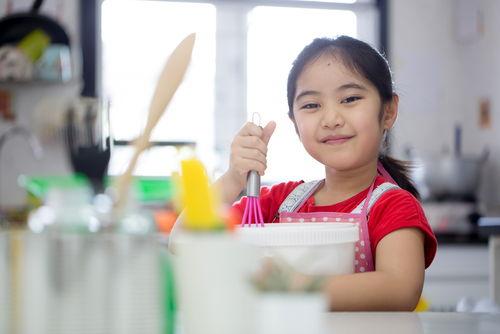 little girl helping make dinner