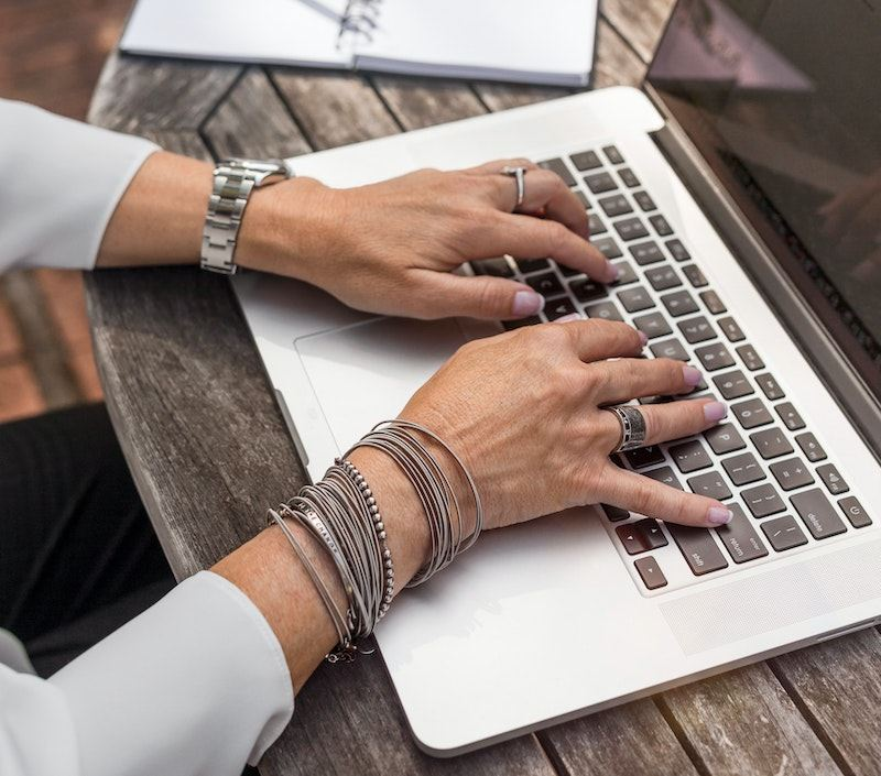 Woman sitting at outdoor wooden table with computer and silver jewlery