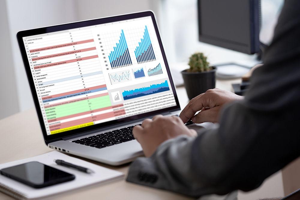 man in suit typing on laptop