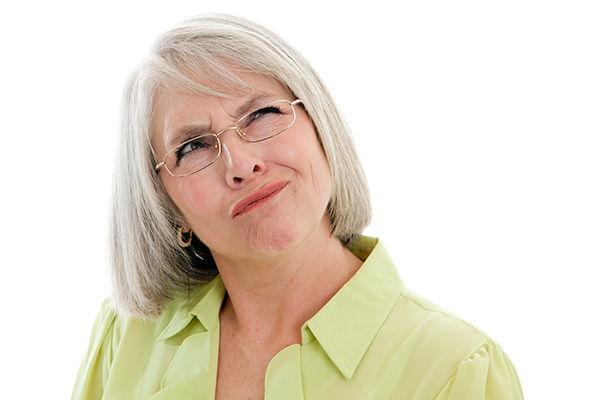 Older woman in glasses looking confused