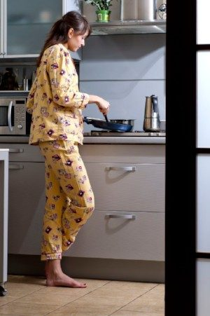 image of young woman cooking in her pajamas