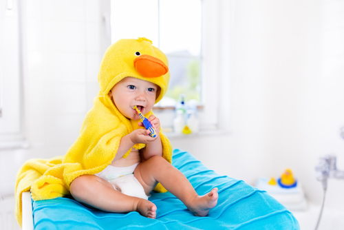 Baby in a yellow duck towel brushing teeth