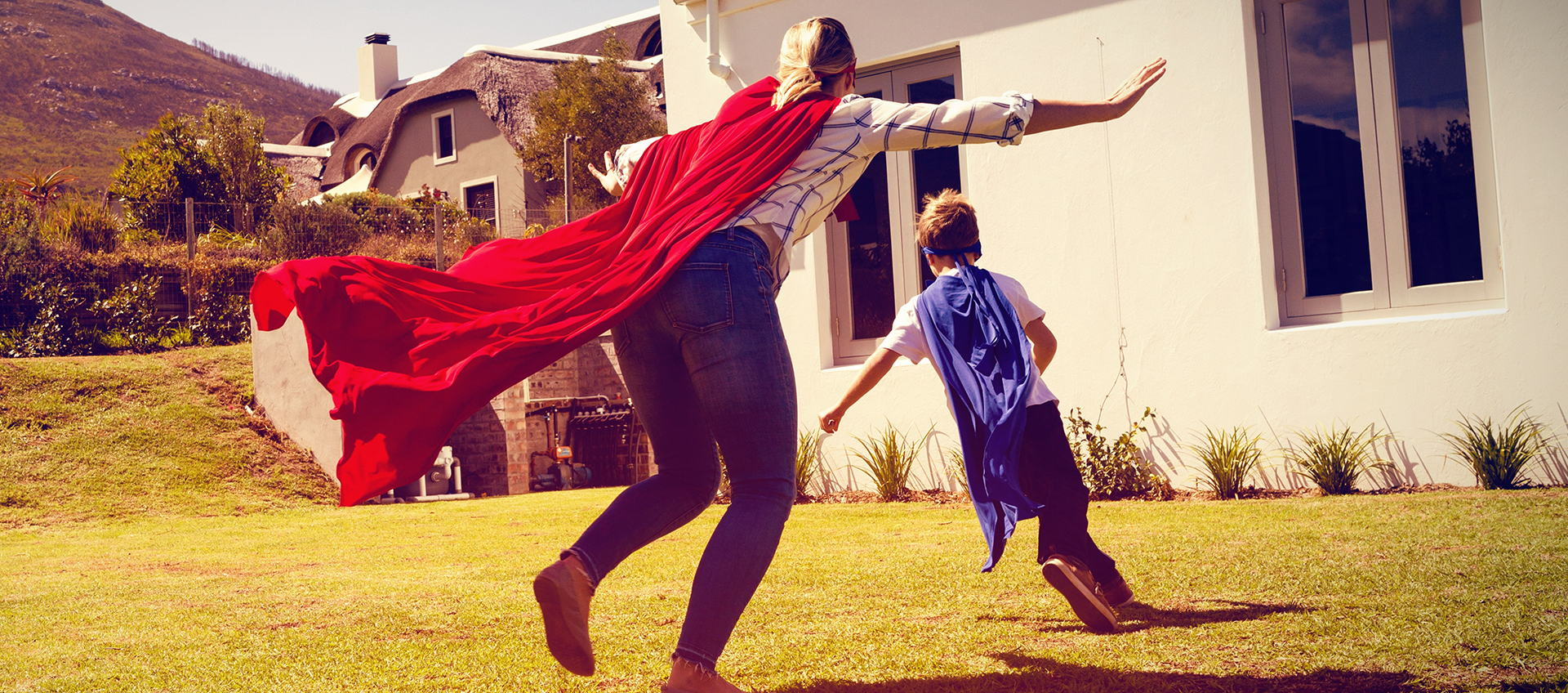 Mother and son in superhero costume playing in backyard