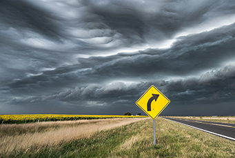 Yellow street sign with curve against a stormy sky.